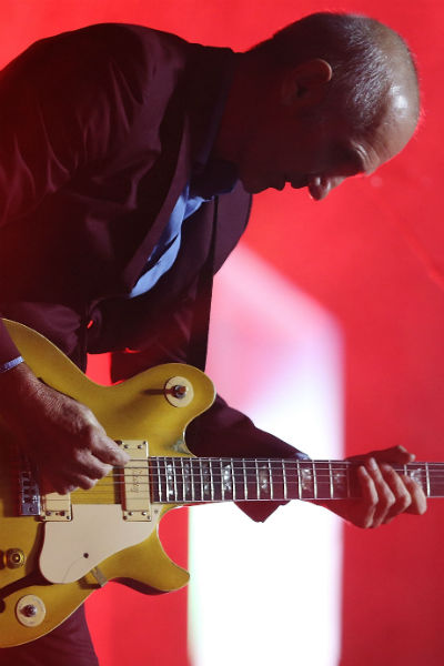 Paul Kelly plays guitar
